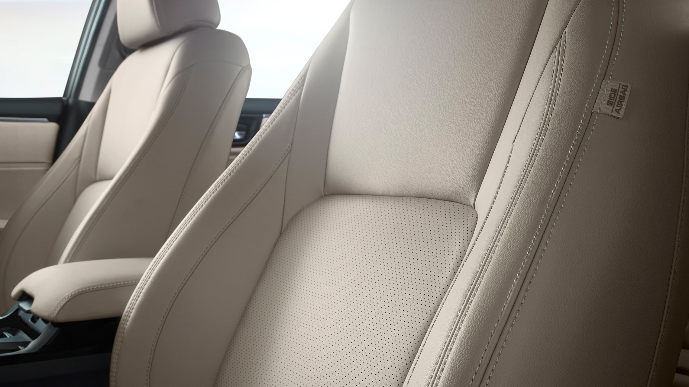 Detail of perforated seating surfaces in Beige Leather.