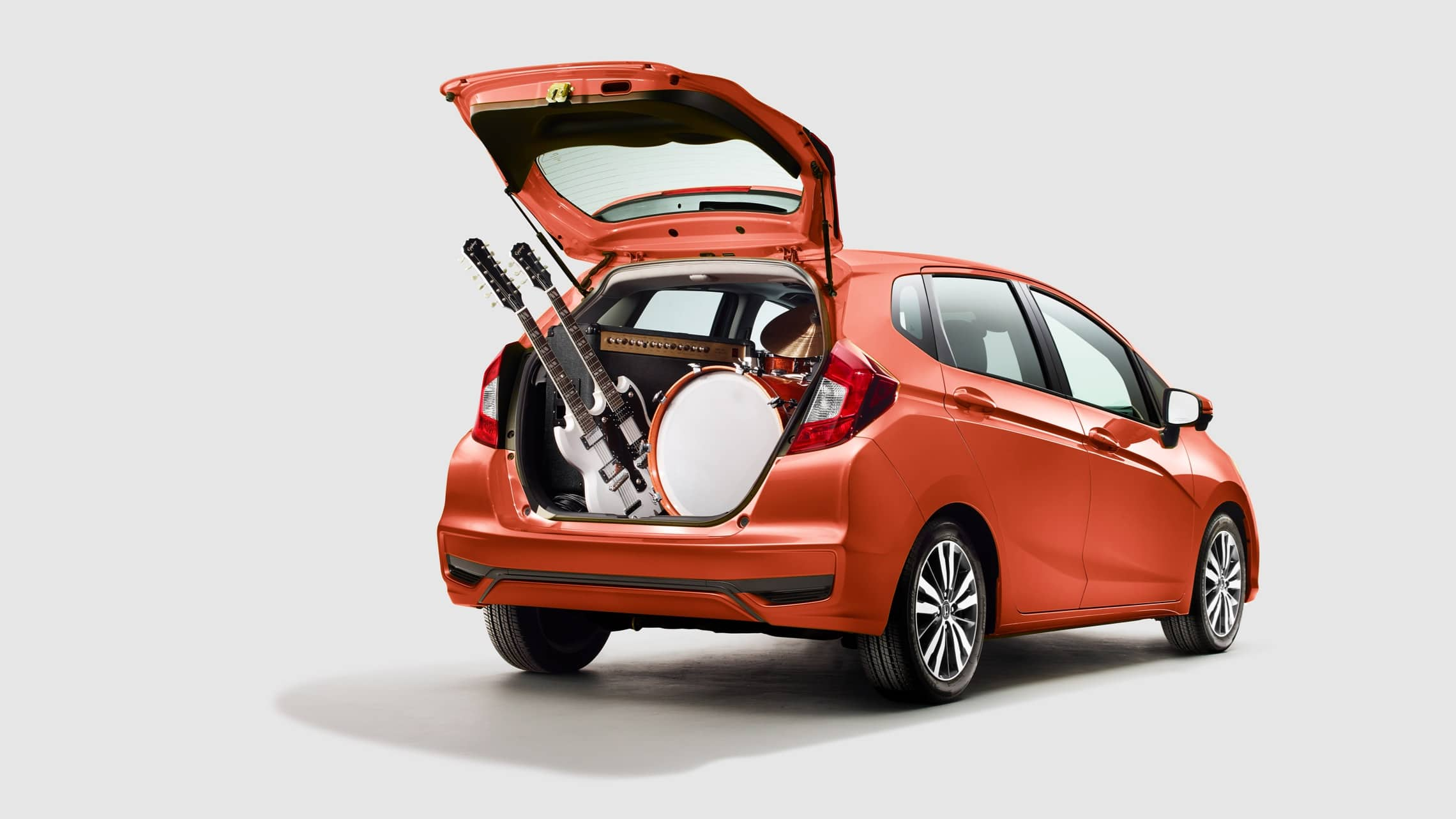 Rear passenger-side view of the 2020 Honda Fit EX-L in Orange Fury with liftgate open and musical instruments in cargo area.